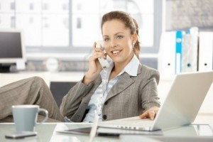 8251350-attractive-businesswoman-sitting-at-desk-talking-on-phone-having-laptop-smiling